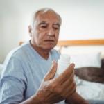 Senior man looking at pill bottle in bedroom